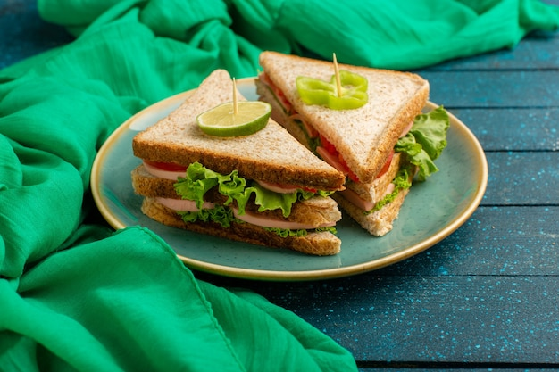Sanduíches de presunto dentro de plateo verde no azul