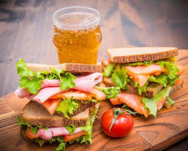 Sanduíches de presunto e salmão defumado com copos de cerveja