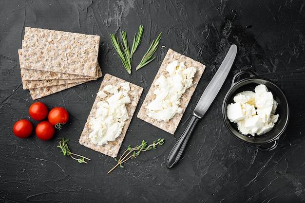 Sanduíches de requeijão com ervas frescas. torrada de pão crocante com queijo cottage, em mesa de pedra preta escura, vista de cima plano