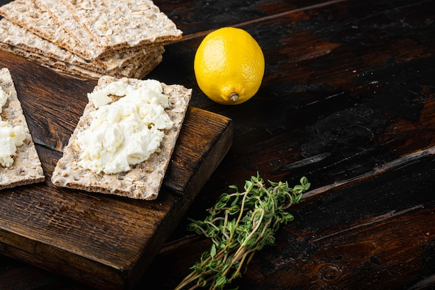 Sanduíches de requeijão com ervas frescas. torrada de pão crocante com queijo cottage, na velha mesa de madeira escura