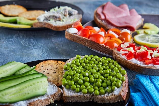 Sanduíches de rosto aberto variados, sanduíches com fatias de fermento com vários recheios em um prato