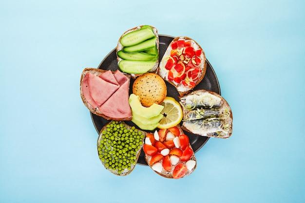 Sanduíches de rosto aberto variados, sanduíches com fatias de fermento com vários recheios em uma superfície azul