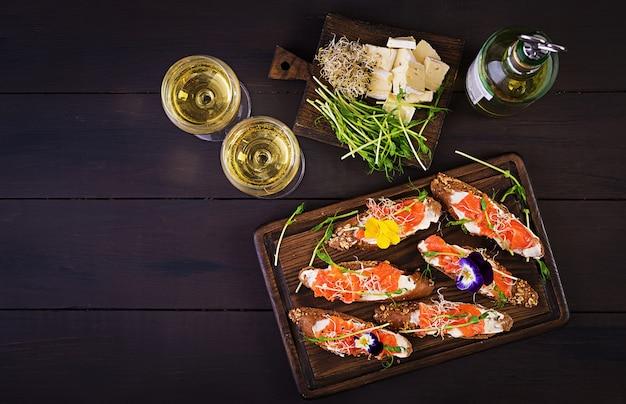 Sanduíches de salmão com creme de queijo e microgreen na mesa de madeira.