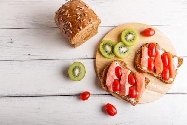 Sanduíches de salmão defumado com manteiga e tomate cereja em branco