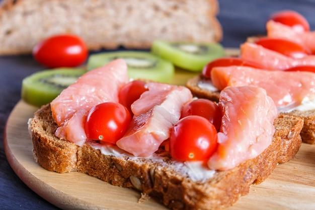 Sanduíches de salmão defumado com manteiga e tomate cereja em fundo preto de madeira
