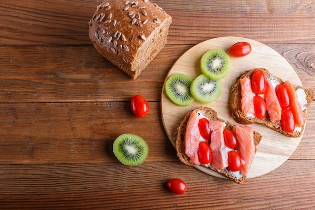 Sanduíches de salmão defumado com manteiga na madeira