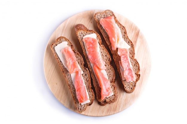 Sanduíches de salmão defumado com manteiga na placa de madeira, isolada no branco