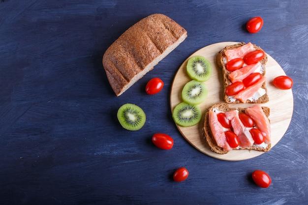 Sanduíches de salmão defumado com manteiga no fundo escuro de madeira.