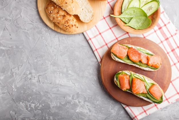 Sanduíches de salmão defumado com pepino e espinafre na placa de madeira