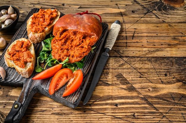 Sanduíches de tapa com sobrassada de linguiça de porco curada e tomate em tábua de madeira
