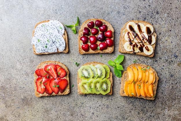 Sanduíches de torradas com manteiga de amendoim, morangos e frutas pêssego, morango, banana, cereja, kiwi e fruta do dragão