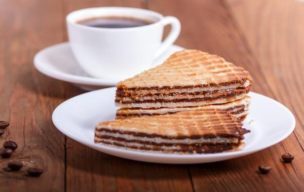 Sanduíches de waffle com leite condensado cozido no prato na mesa de madeira marrom com copo