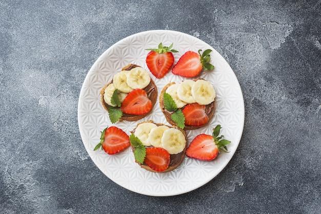 Sanduíches deliciosos com nougat, morango e banana do chocolate.