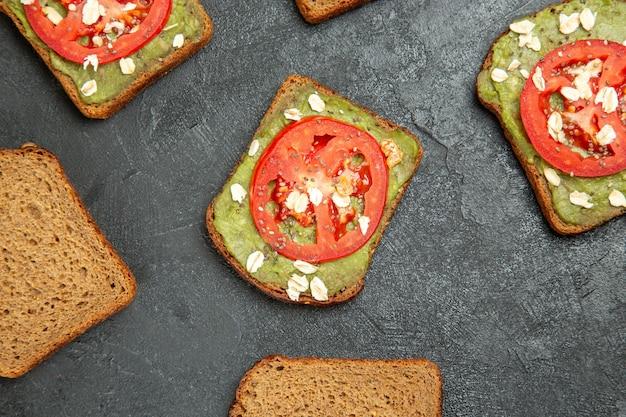 Sanduíches deliciosos com wassabi e tomate vermelho na superfície cinza