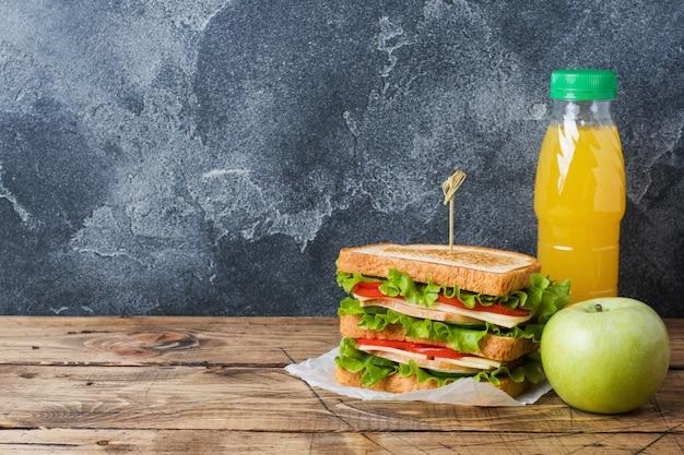 Sanduíches deliciosos e frescos, maçã fresca e suco de laranja