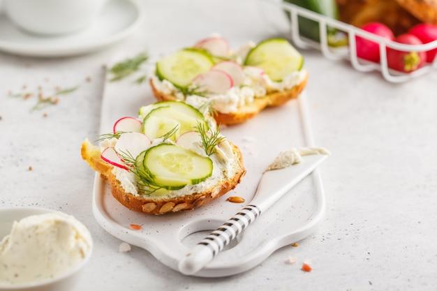 Sanduíches do queijo creme, do pepino e do rabanete do café da manhã em uma placa branca.