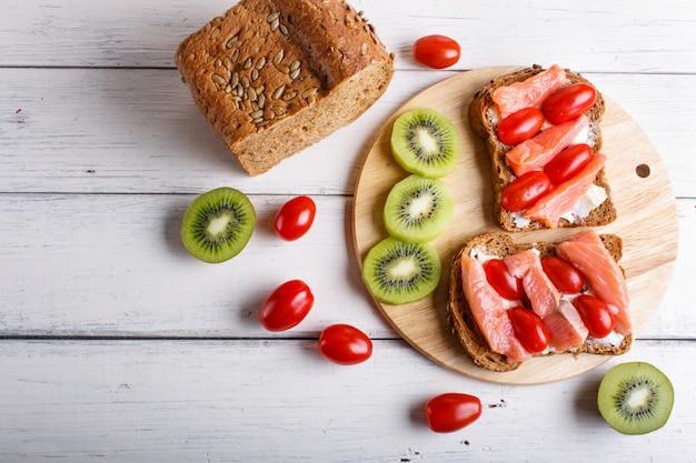 Sanduíches do salmão fumado com manteiga e tomates de cereja no fundo de madeira branco.