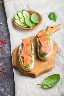 Sanduíches do salmão fumado com pepino e espinafres na placa de madeira em um fundo de linho.