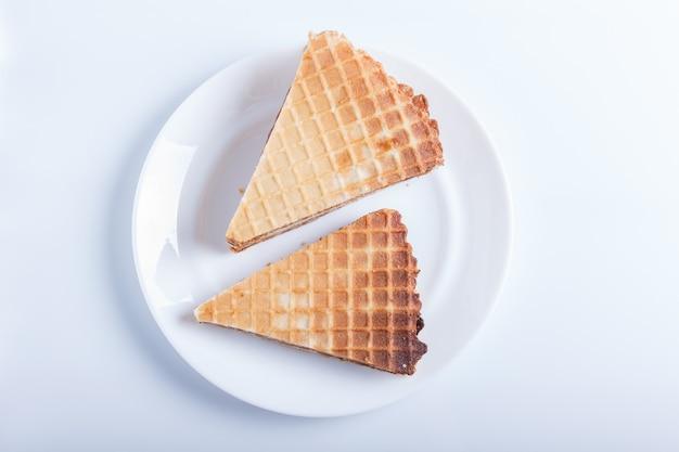 Sanduíches do waffle com leite condensado fervido na placa isolada no fundo branco.