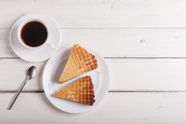 Sanduíches do waffle com leite condensado fervido na placa na tabela de madeira branca com xícara de café. vista do topo