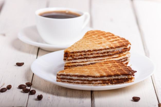 Sanduíches do waffle com leite condensado fervido na placa na tabela de madeira branca com xícara de café.