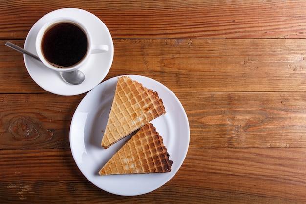Sanduíches do waffle com leite condensado fervido na placa na tabela de madeira marrom com xícara de café. vista do topo