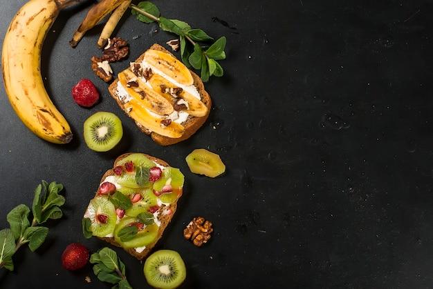Sanduíches doces saborosos com bananas, nozes e chocolate, kiwi, morangos e hortelã no preto