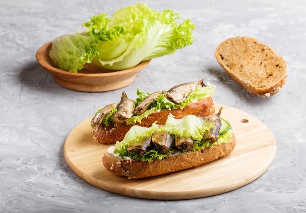Sanduíches dos arenques pequenos com alface e queijo creme na placa de madeira em um concreto cinzento.
