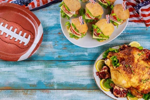 Sanduíches e frango assado inteiro para os fãs do jogo de futebol americano.