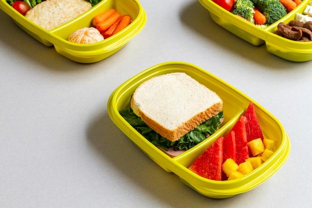 Sanduíches e frutas embalados de alto ângulo