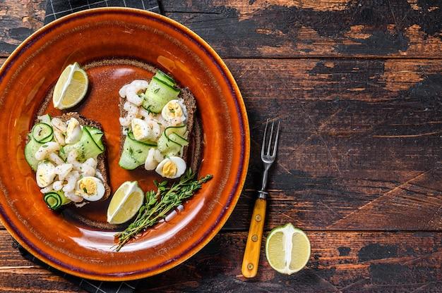 Sanduíches escandinavos com camarão, camarão, ovo de codorna e pepino no pão de centeio. escuro