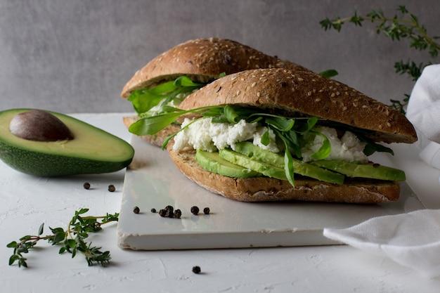 Sanduíches feitos de pão integral com abacate e ricota.