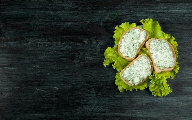 Sanduíches frescos com legumes em uma placa escura em uma superfície texturizada.