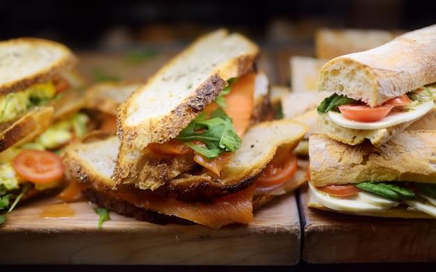 Sanduíches frescos na tábua de madeira nas vitrines do café ou restaurante