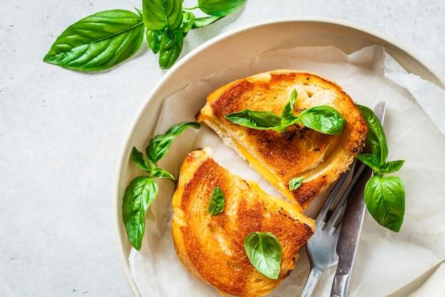 Sanduíches fritos com queijo e manjericão na chapa branca.