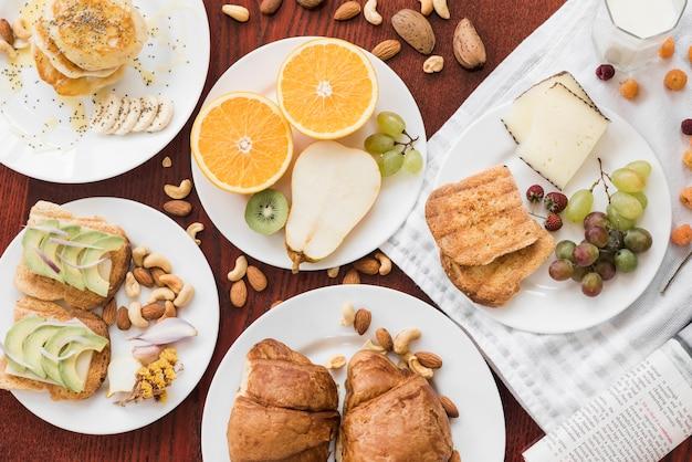 Sanduíches; frutas; frutas secas no prato sobre a mesa de madeira