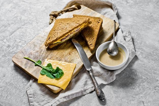 Sanduíches grelhados com queijo, pão preto, carne de peru e rúcula.