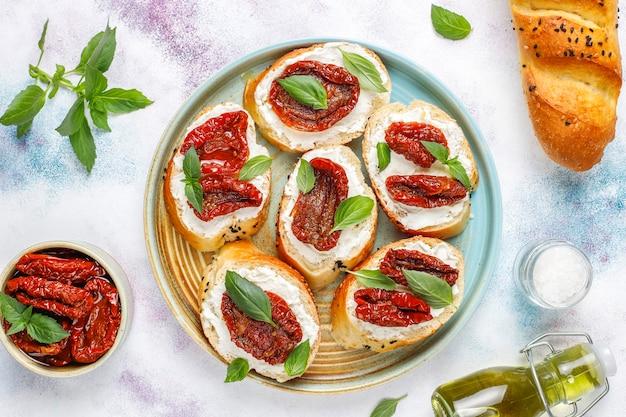 Sanduíches italianos - bruschetta com queijo, tomate seco e manjericão.