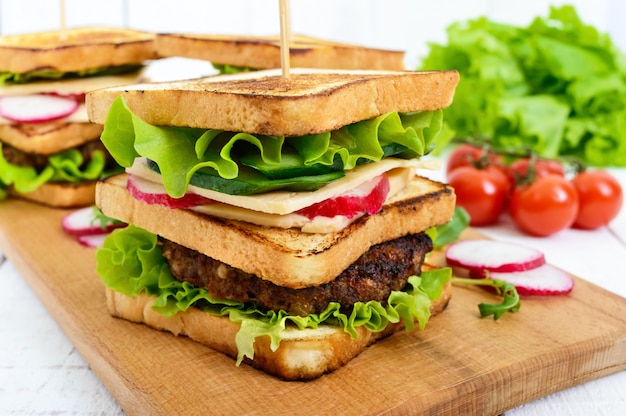 Sanduíches multicamadas com uma costeleta suculenta, queijo, rabanete, pepino, alface, rúcula em uma placa de corte