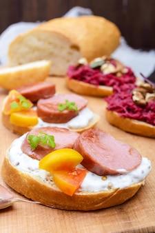 Sanduíches no café da manhã com linguiça frita, tomate amarelo, molho cremoso de mostarda em uma tábua de cortar