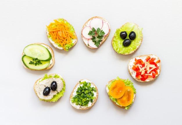 Sanduíches ou tapas de pão branco com deliciosos ingredientes saudáveis em fundo branco.