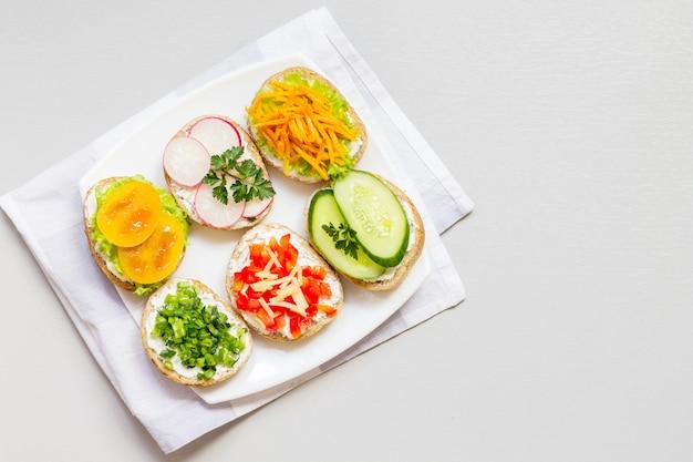 Sanduíches ou tapas de pão branco com deliciosos ingredientes saudáveis em um guardanapo, sobre um fundo branco.
