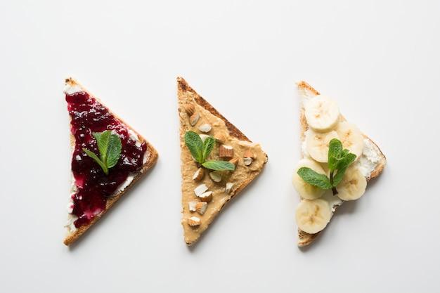 Sanduíches para o café da manhã infantil saudável e sem açúcar, pasta de nozes, banana, geléia de frutas silvestres.