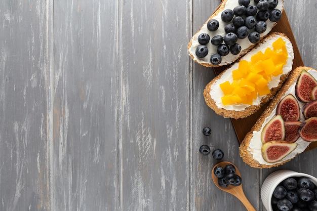 Sanduíches planos com cream cheese e frutas com espaço de cópia