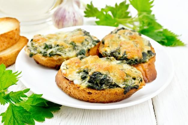 Sanduíches quentes com urtiga e queijo em fatias de pão de trigo em um prato, alho em um fundo de tábua de madeira