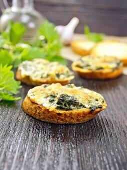 Sanduíches quentes com urtiga e queijo em fatias de pão de trigo no fundo de tábuas de madeira escuras
