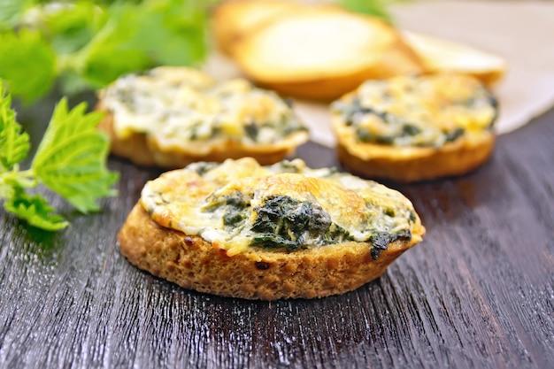 Sanduíches quentes com urtiga e queijo nas fatias de pão de trigo