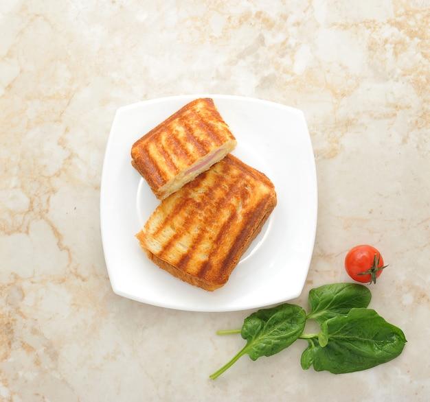 Sanduíches quentes em um prato com folhas de espinafre e tomate cereja
