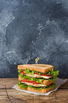 Sanduíches saborosos e frescos em uma mesa de madeira escura. copie o espaço.