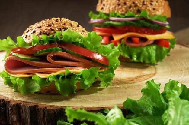 Sanduíches saborosos e frescos em uma mesa de madeira